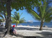 Tim Fitzharris - Tourist resting under palm trees on beach at Palmetto Bay, Roatan Island, Honduras