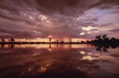 Gerry Ellis - Sunset and storm clouds over waterhole, Linyanti Swamp, Botswana