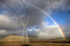 Colin Monteath - Powerlines, rainbow forms as evening sun lights up rain clouds, Canterbury, New Zealand