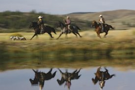 Konrad Wothe - Cowboys riding Horses with dogs running beside pond, Oregon