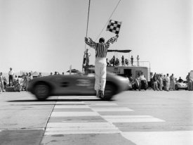 H. Armstrong Roberts - Man jumping waving checkered flag